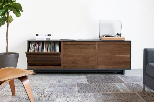 AERO 76 LP Shelves made from North American hardwood. Features 3 flip-style record storage bins with room for 120 LPs. Sitting on top of the walnut wood cabinet is a hi-fi turntable and coffee table books and decorations.