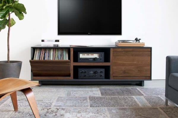 AERO 76 LP Shelves made from North American hardwood. Features 2 flip-style record storage bins (pulled down in display setting) with room for 120 LPs. Middle shelf includes two hi-fi audio equipment consoles. Features a Walnut finish and sits in a living room setting under a hanging tv.