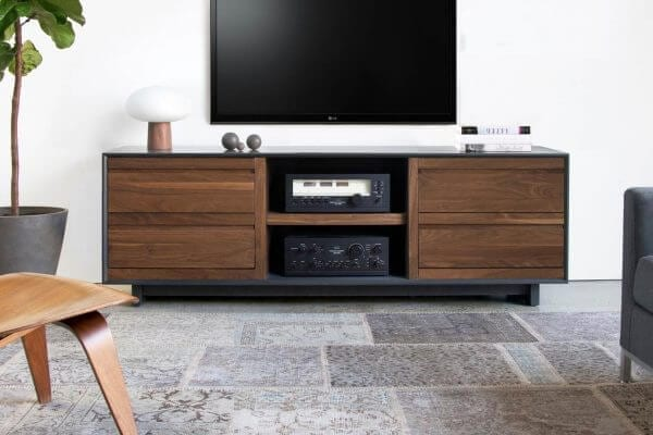 AERO 76 LP Shelves made from North American hardwood. Features 2 flip-style record storage bins with room for 120 LPs. Middle shelf includes two hi-fi audio equipment consoles. Features a Walnut finish and sits in a living room setting under a hanging tv.