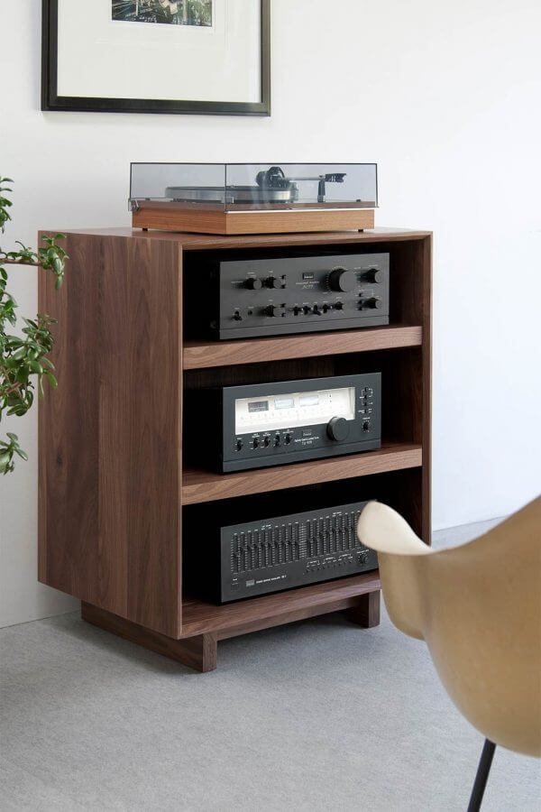 AERO Audio Rack Walnut that is 3 shelves high with hi-fi audio equipment on each shelf. It features a dark walnut finish and is sitting in a living room setting.