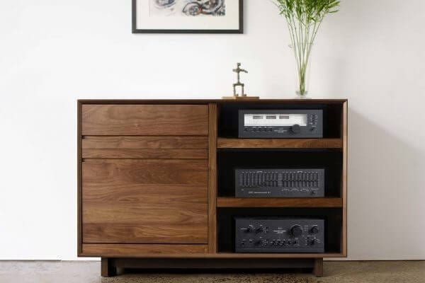 AERO 51 LP Storage Console made from North American hardwood. Features a flip-style record storage bin with room for 120 LPs in a closed position. The right side drawers have room for 3 hi-fi audio equipment as well as the top shelf. It features a Walnut finish and is sitting in a living room setting.