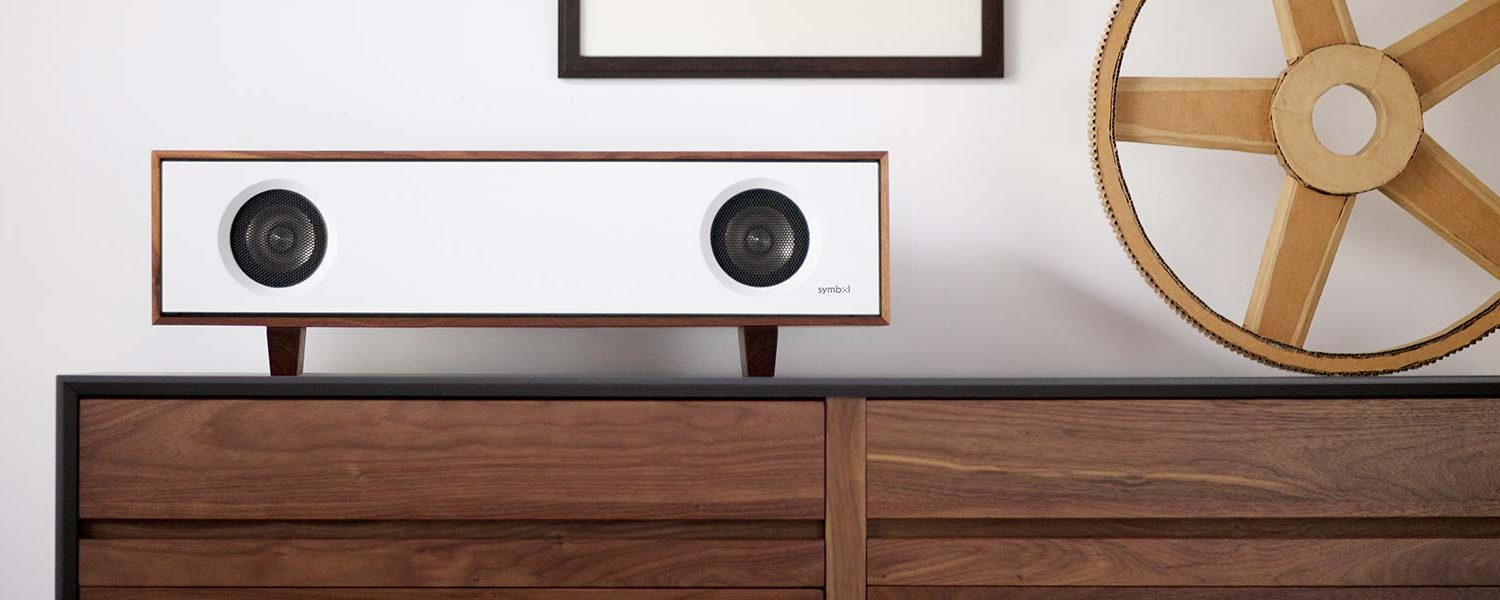 Table Top Hifi Bluetooth speaker on walnut hardwood record storage cabinet in a living room setting.
