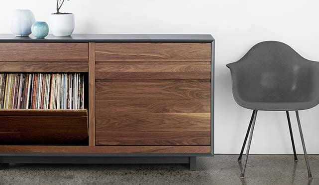 The AERO Entertainment Cabinet is handcrafted with North American hardwoods. Includes two swivel-style LP storage bins. Features room for Hi-Fi audio equipment. Is sitting in a living room setting.